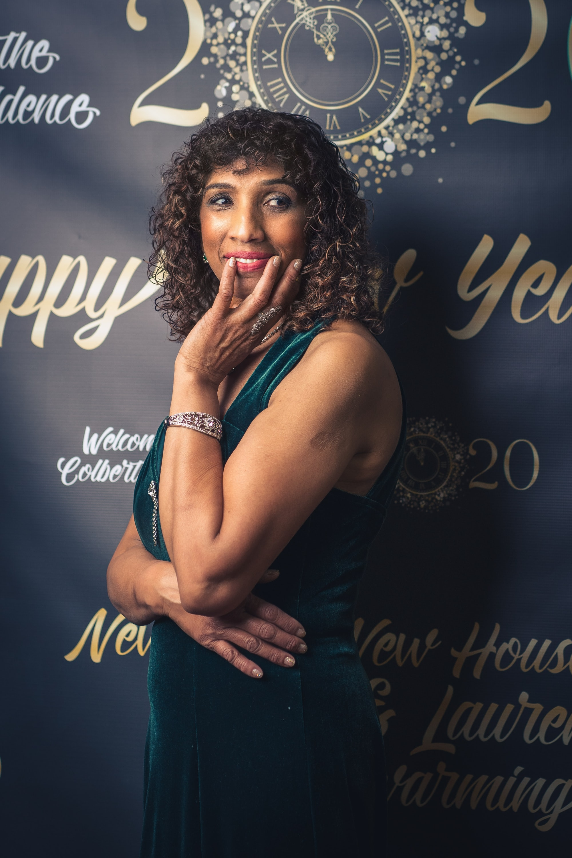 Woman wearing a green dress and getting ready for a new years party.