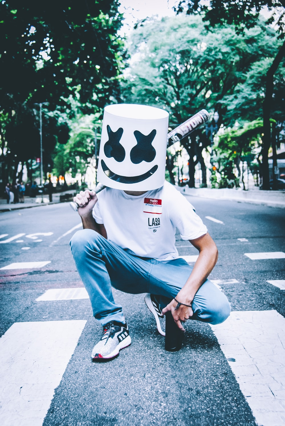 man in white crew neck t-shirt and blue denim jeans wearing white and black mask