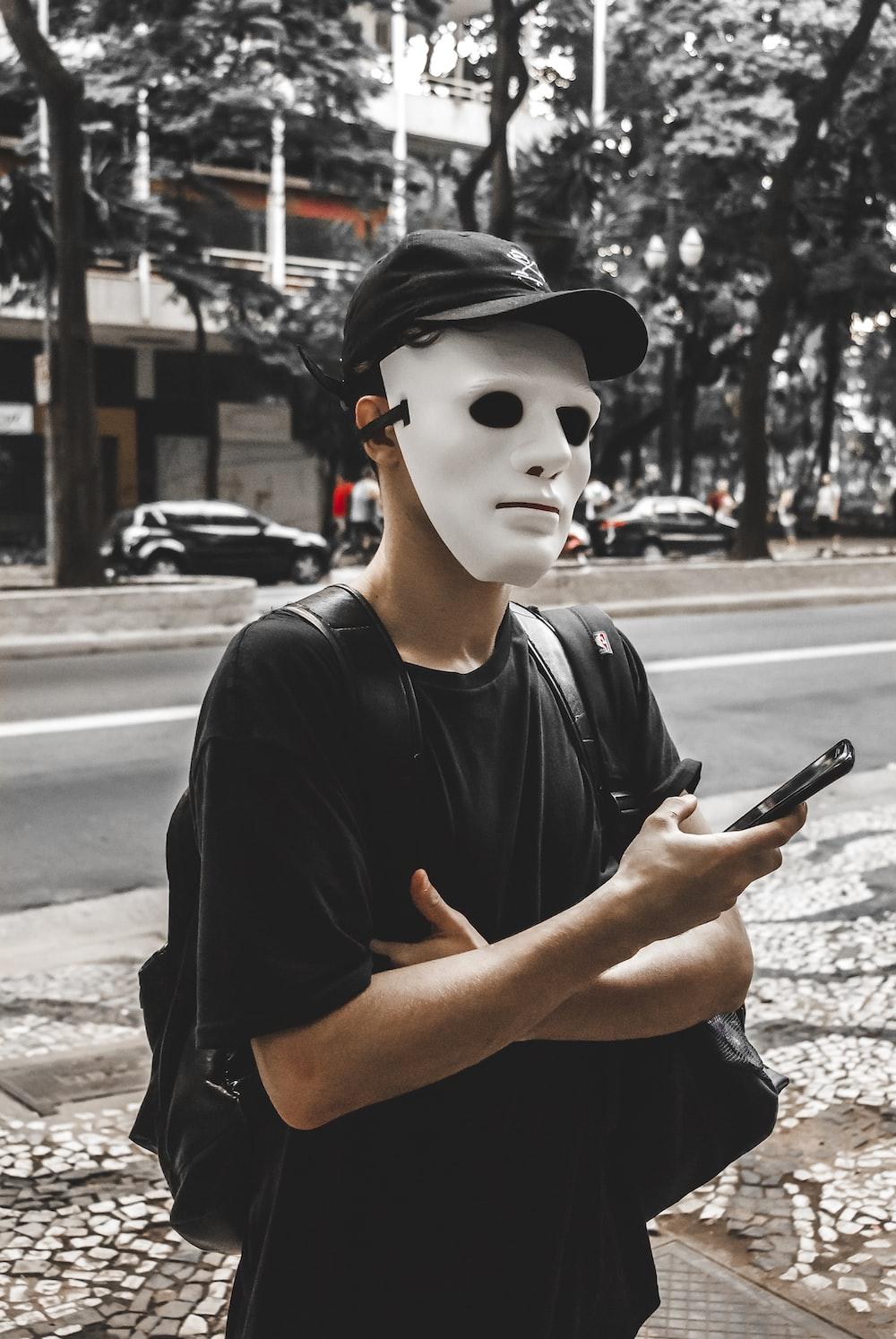 man in black crew neck t-shirt wearing white mask