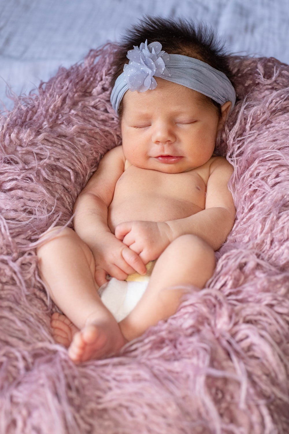 baby lying on pink textile