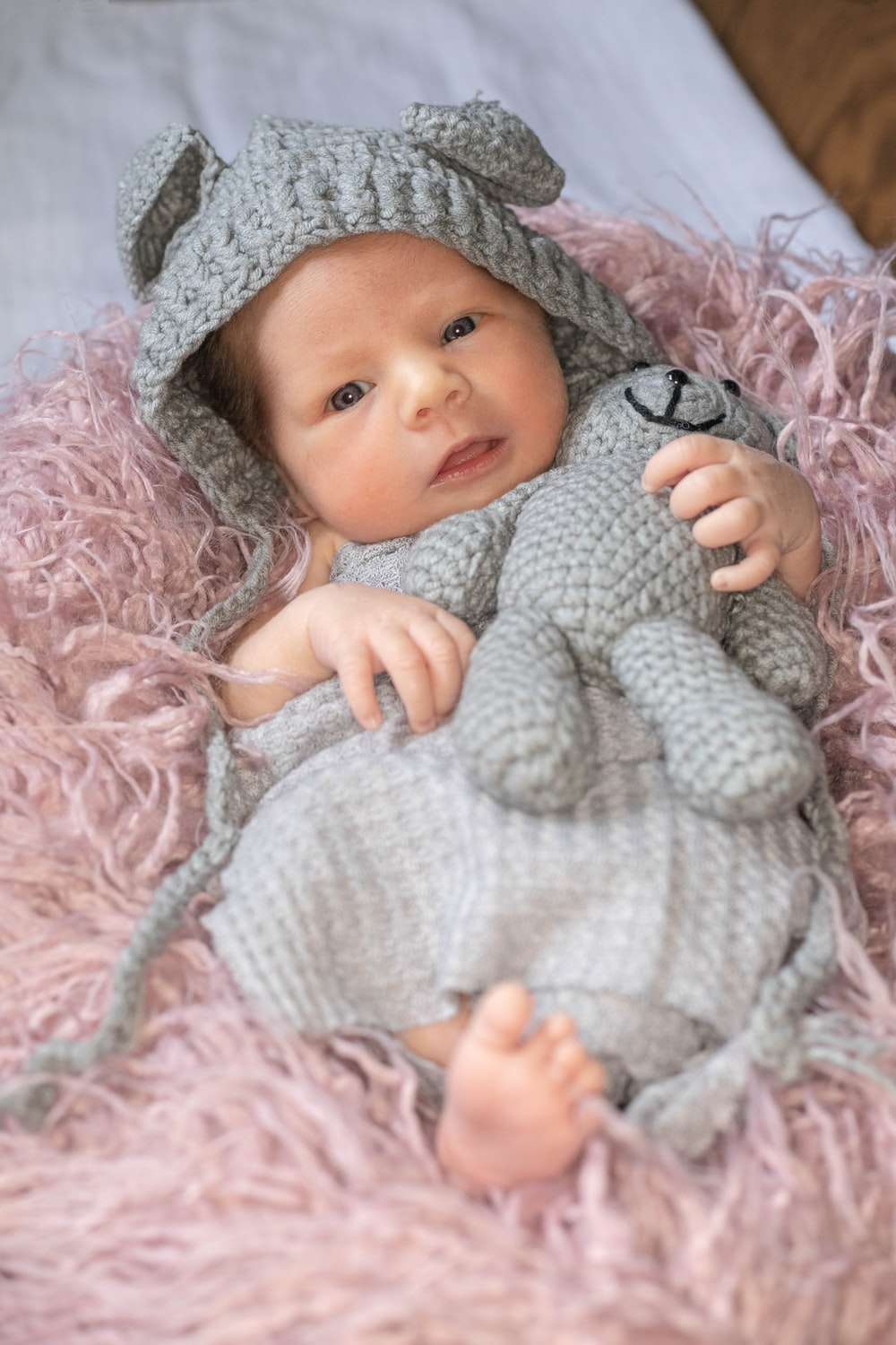 baby in white knit sweater lying on pink textile