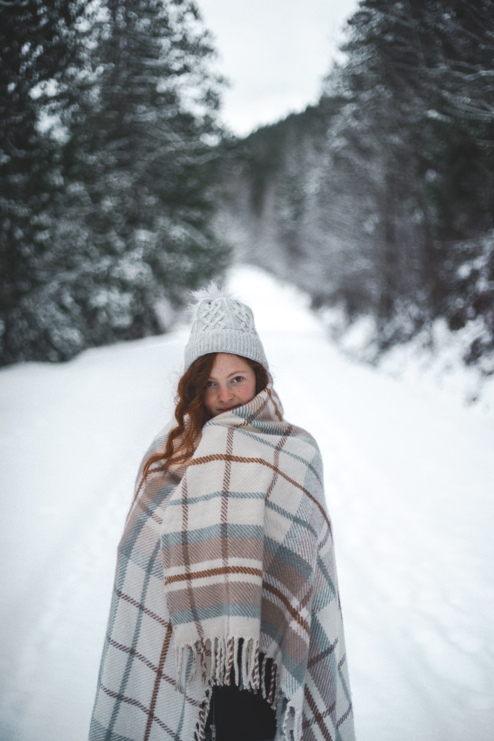 woman in white knit cap standing on snow covered ground during daytime