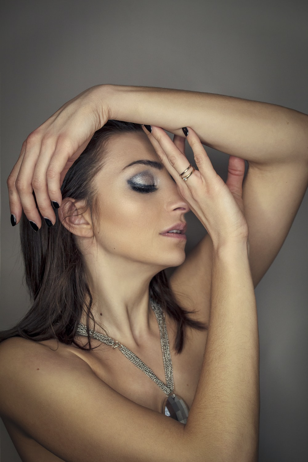 woman in silver necklace covering her face with her hand