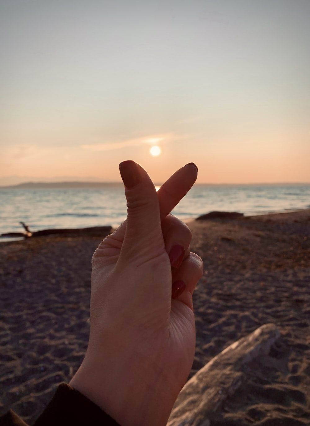 person showing right hand near body of water during sunset