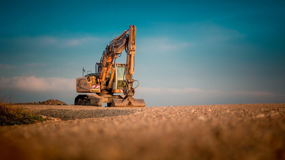 yellow and black excavator on brown sand during daytime