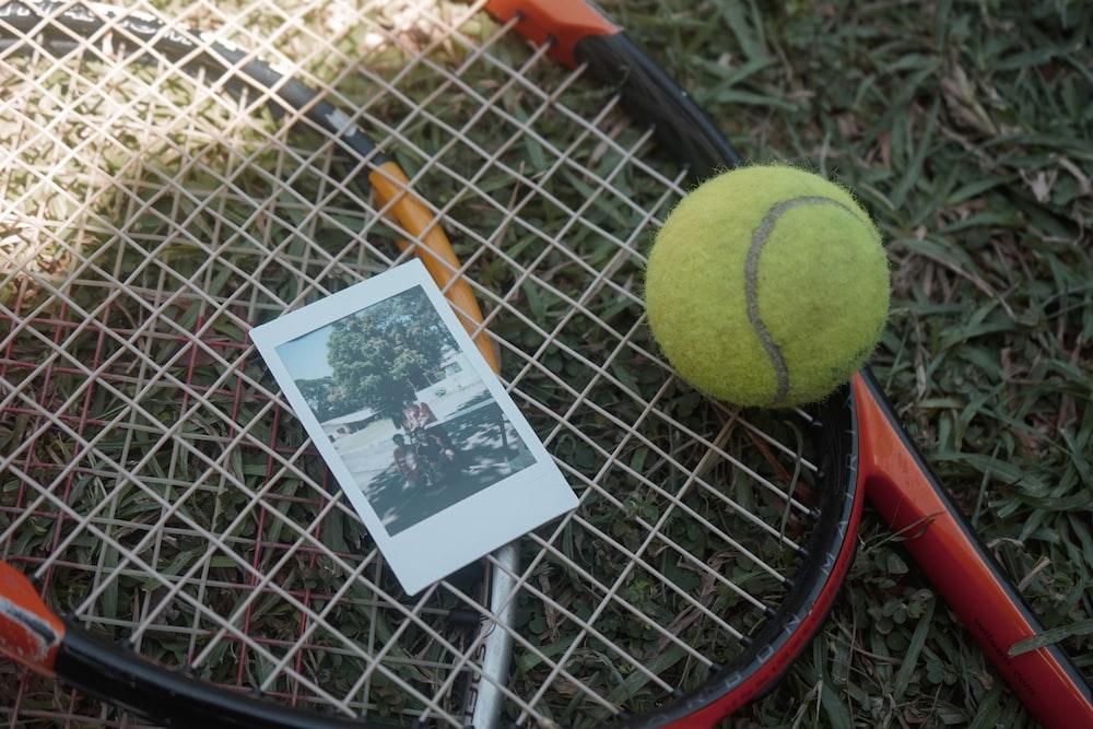 green tennis ball beside white and black card