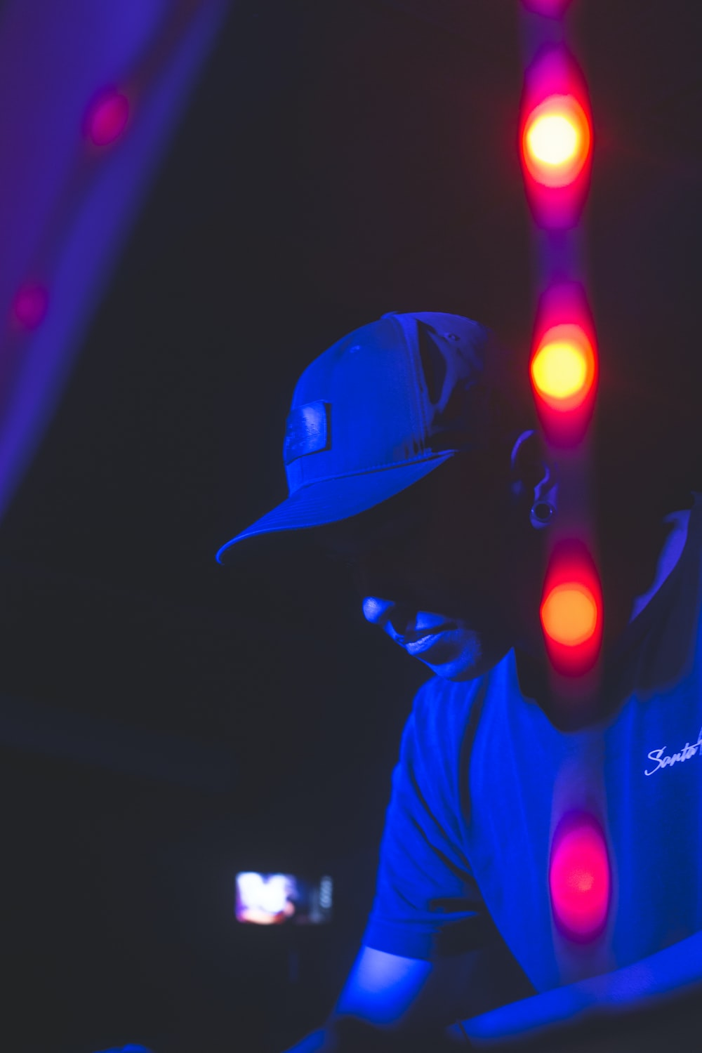 man in black hat and blue and red led lights