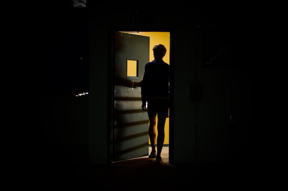 man in black jacket standing in front of white wooden door