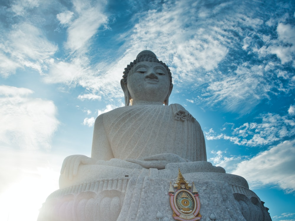 low angle photography of buddha statue under blue sky during daytime
