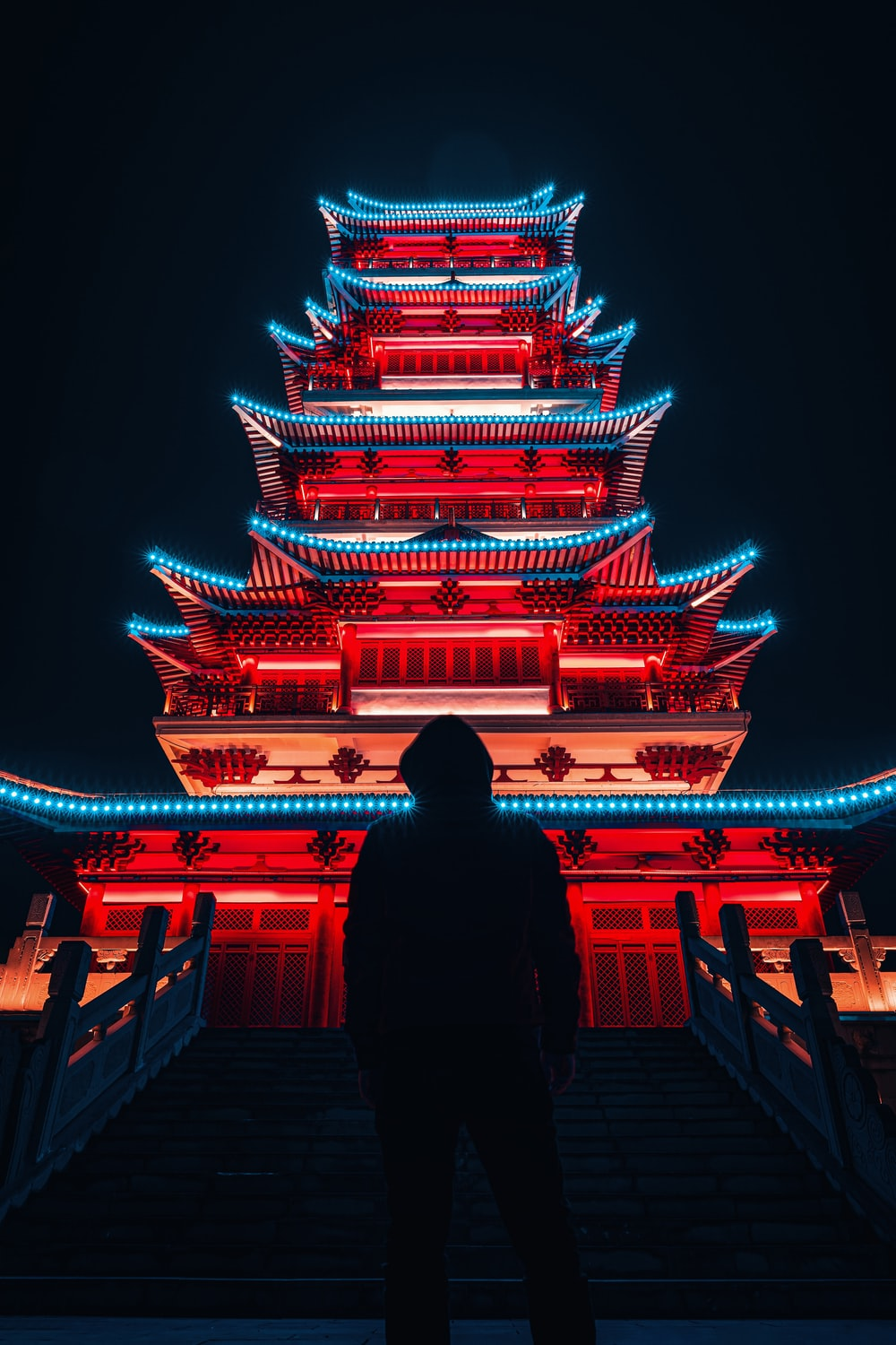 woman in black long sleeve shirt standing in front of temple during nighttime