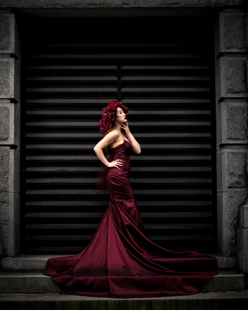 woman in red dress standing near brown brick wall
