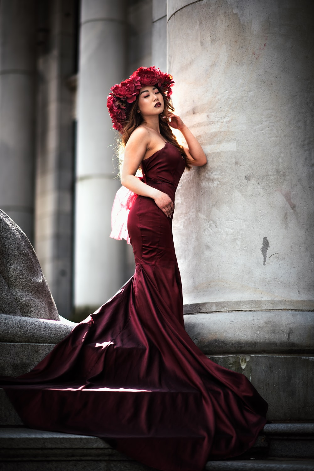 woman in red tube dress leaning on gray concrete wall