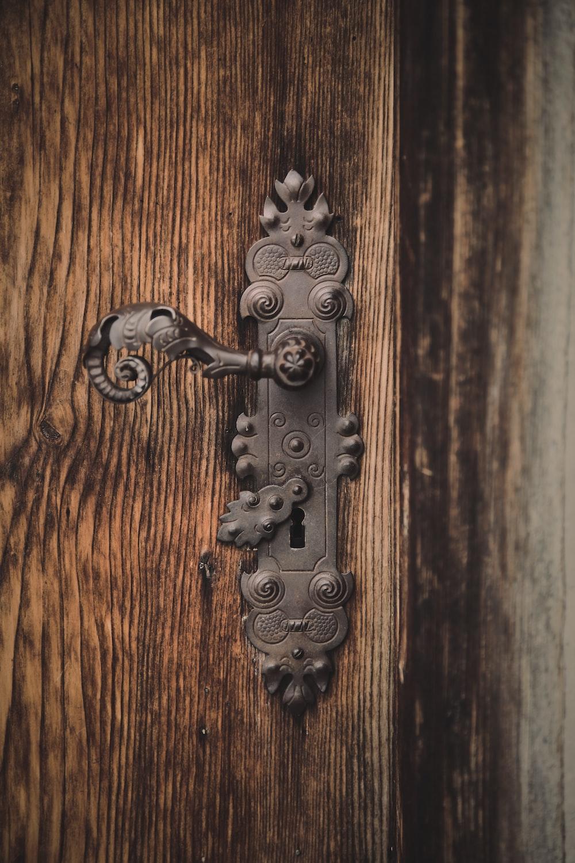 black metal door handle on brown wooden door