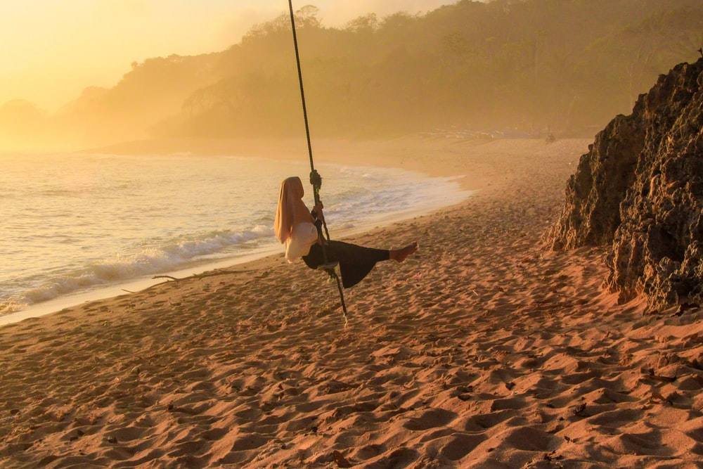 woman in white dress sitting on swing on beach during daytime