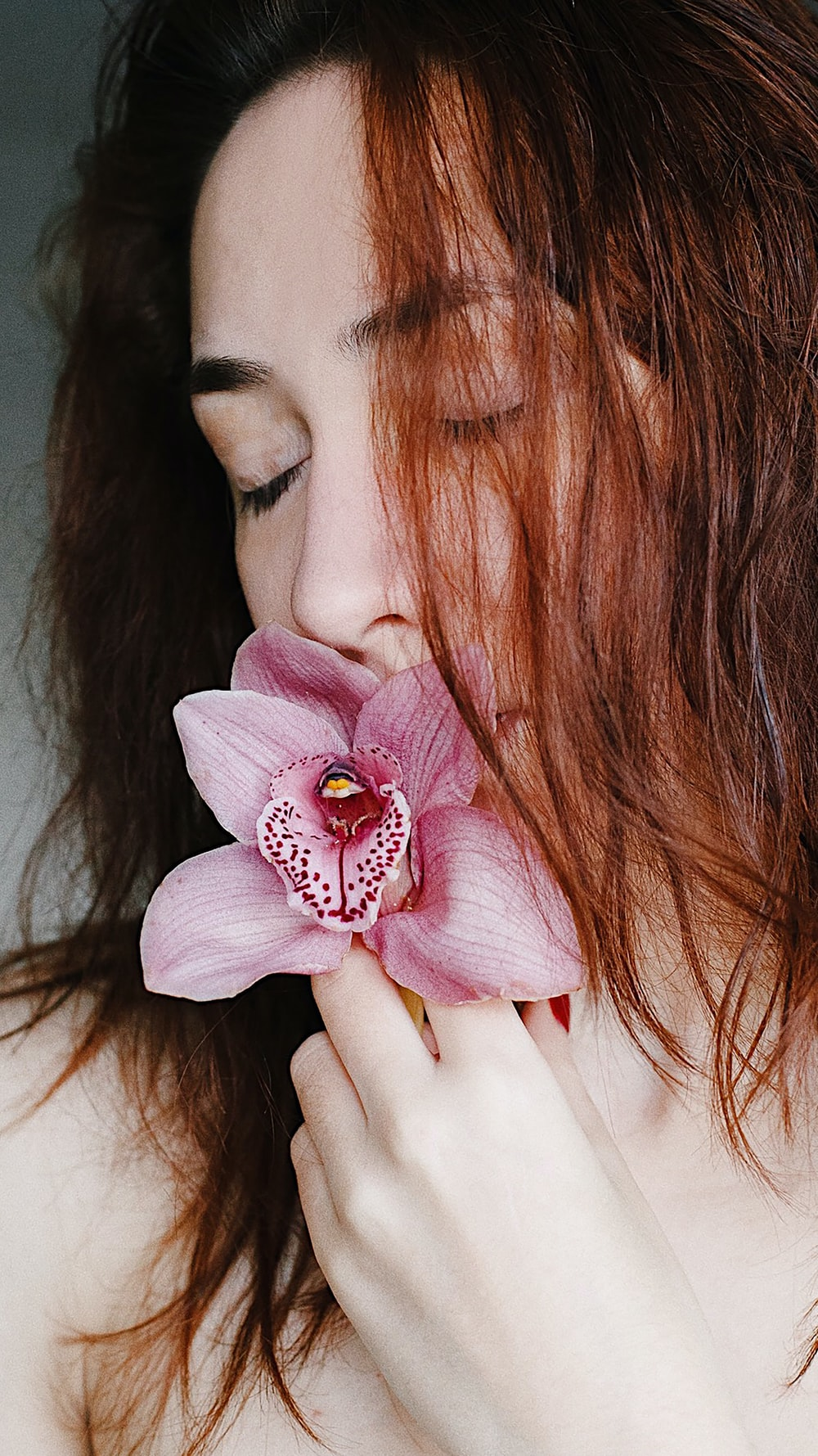 woman with pink flower on her ear
