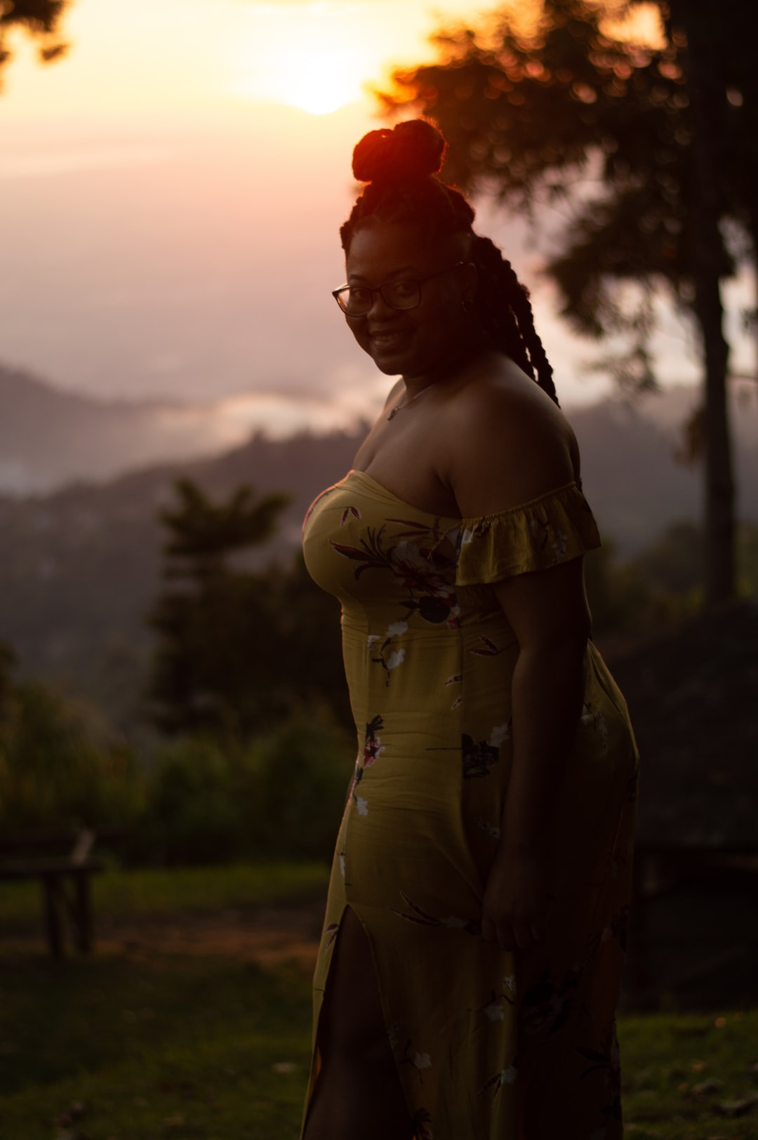 Young millennial women of color (black woman) @shanicejdouglas wearing a yellow floral dress with natural hair, and glasses smiling during sunset in Blue Mountains, Kingston, Jamaica.
