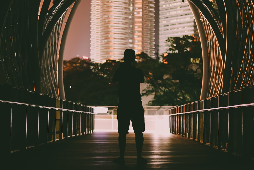 silhouette of man standing on bridge during daytime