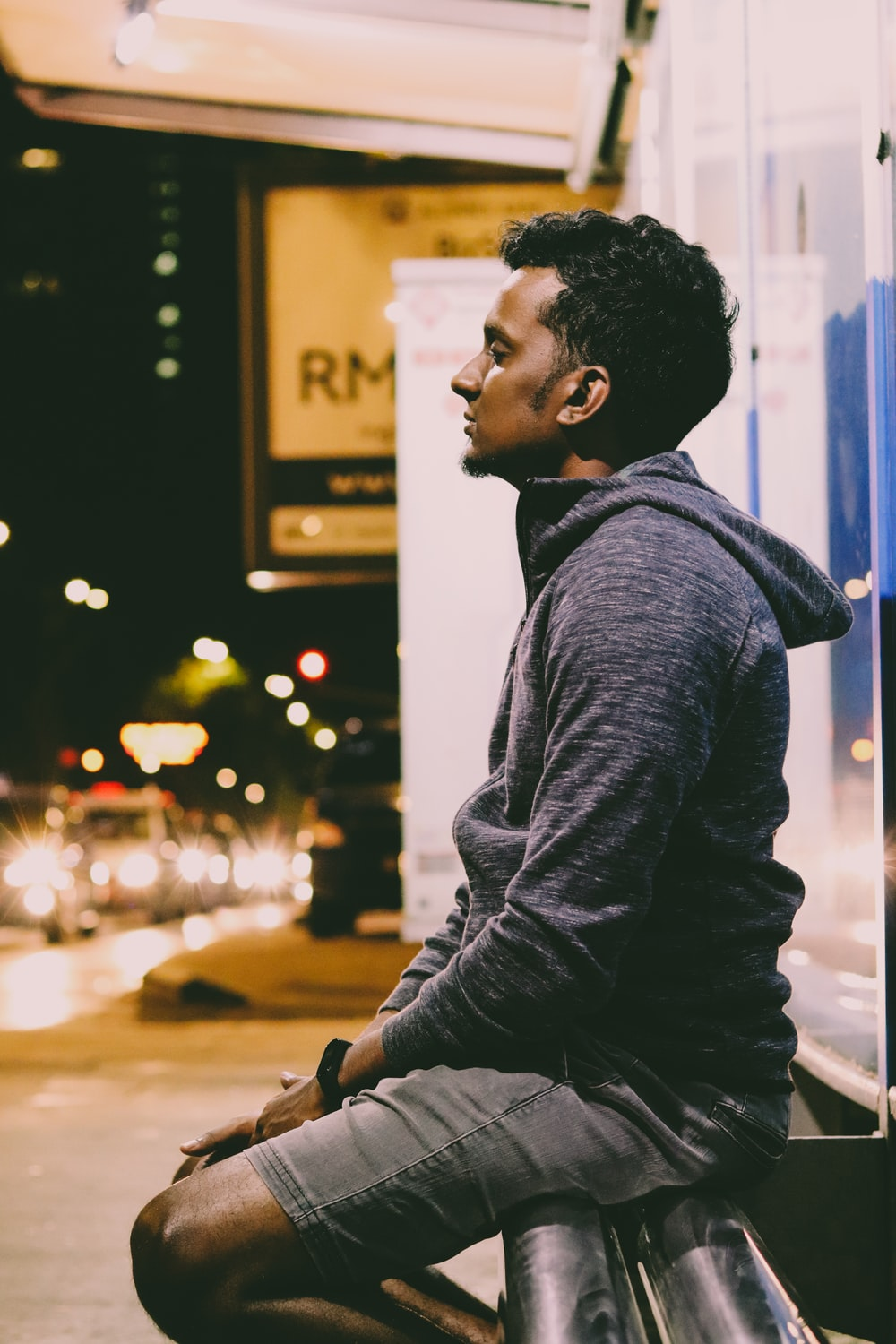 man in black leather jacket sitting on the sidewalk during night time