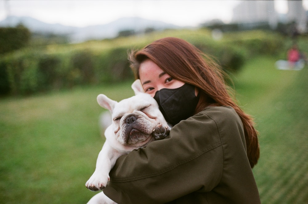 woman in brown jacket kissing white and black short coated puppy