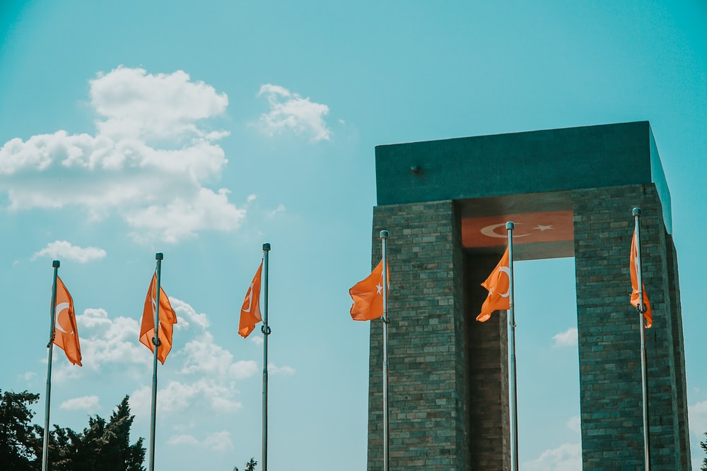 three flags on gray concrete wall under white clouds and blue sky during daytime