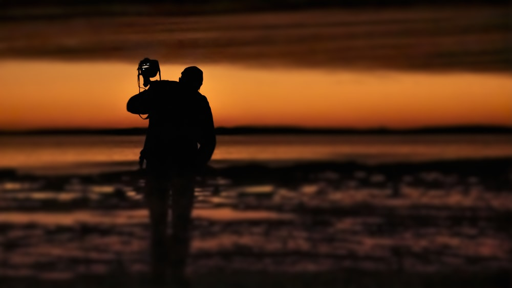 silhouette of 2 person on water during sunset