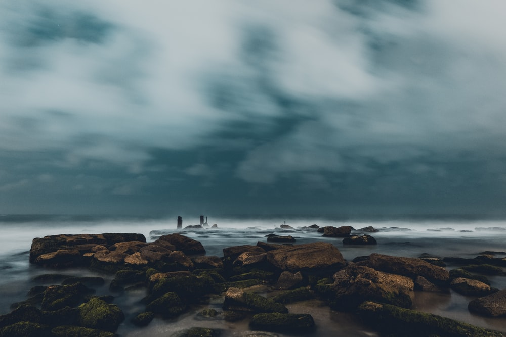 person standing on rocky shore under cloudy sky during daytime