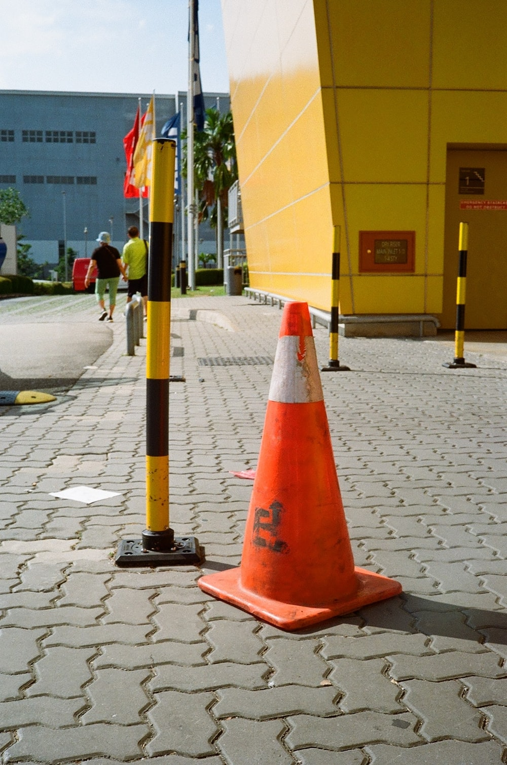 red and black traffic cone on gray concrete pavement