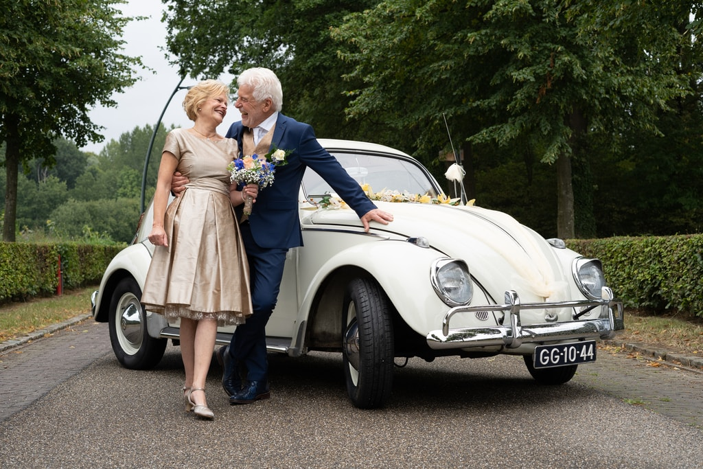 couple standing beside white car during daytime