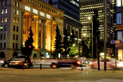 cars on road near high rise building during night time greek revival zoom background