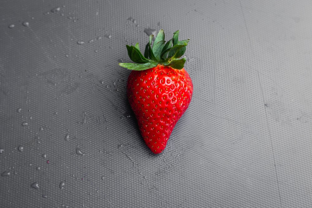 red strawberry on gray textile