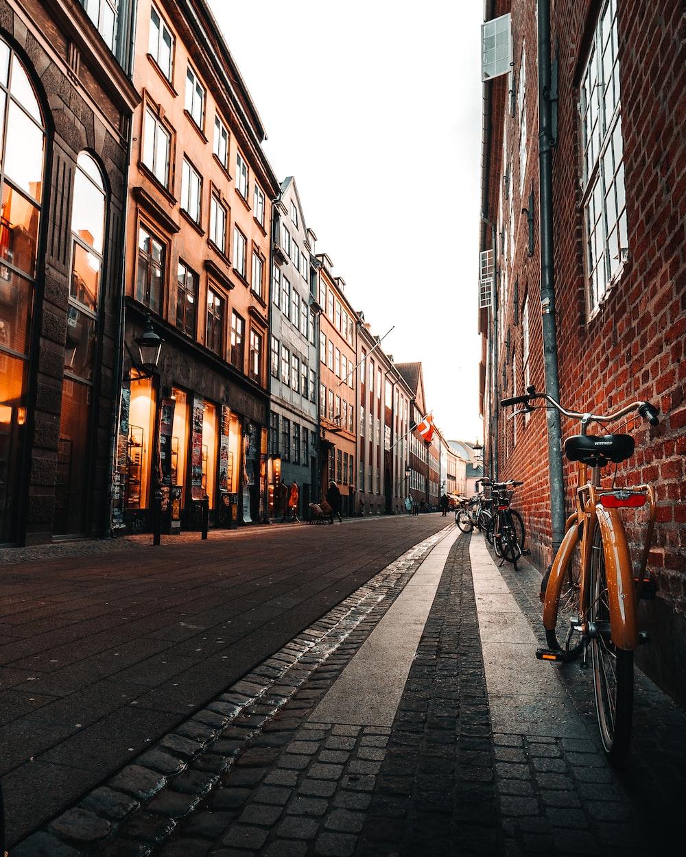 black bicycle parked on sidewalk in between buildings during daytime