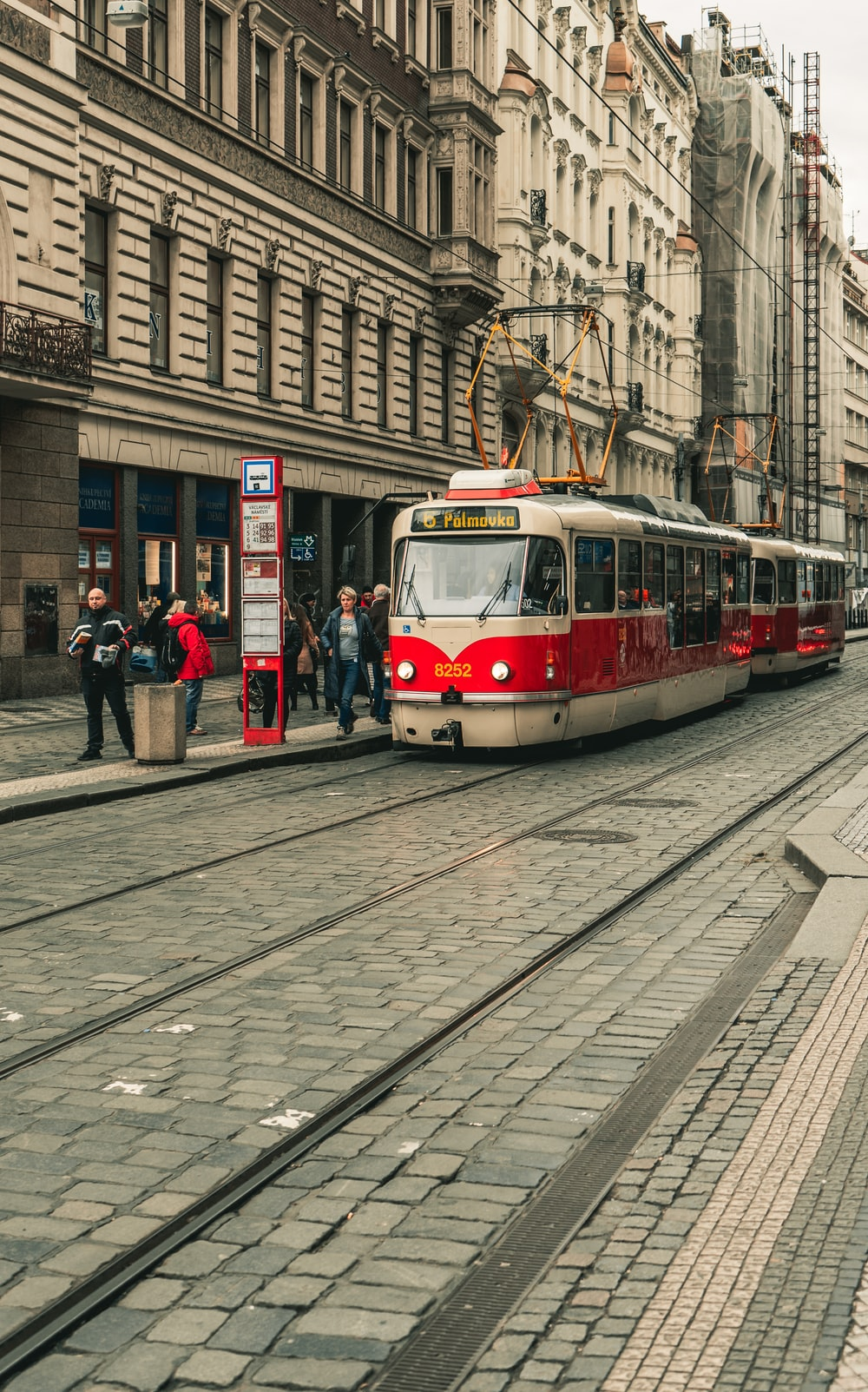 red and white tram on the street during daytime