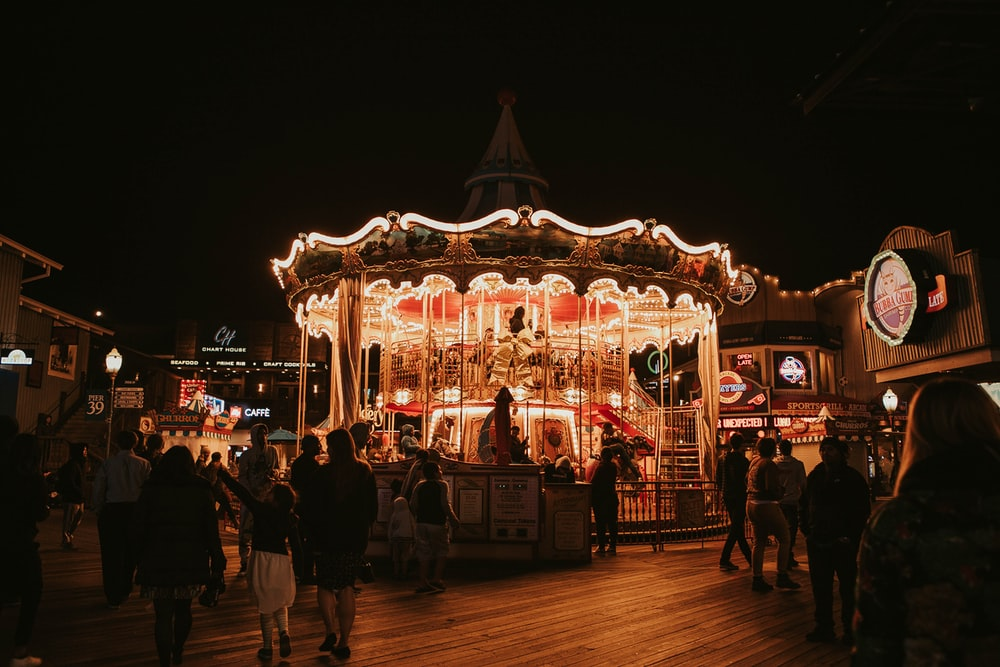 people standing near lighted carousel during night time