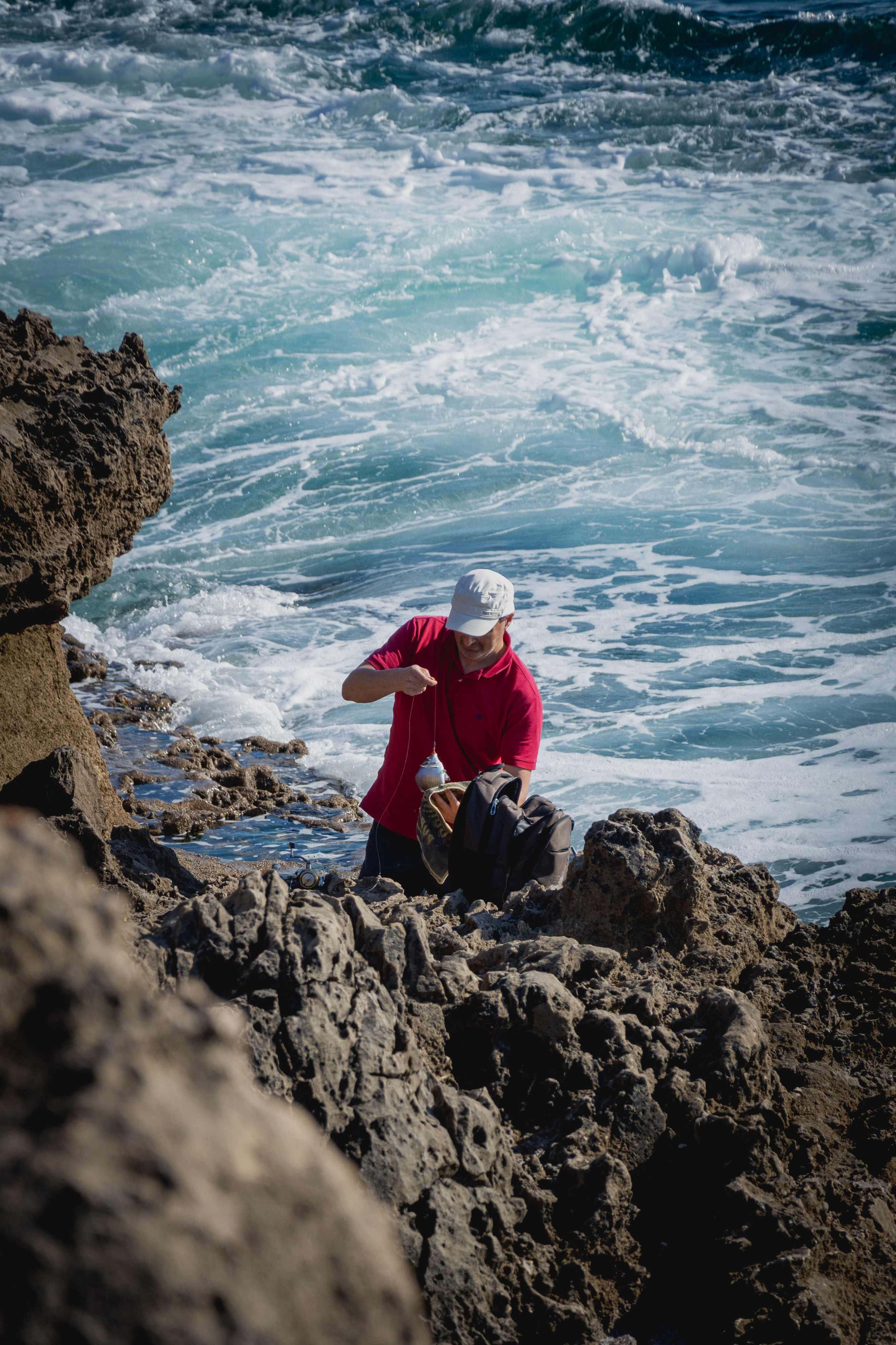 man in red jacket sitting on rock formation near sea during daytime