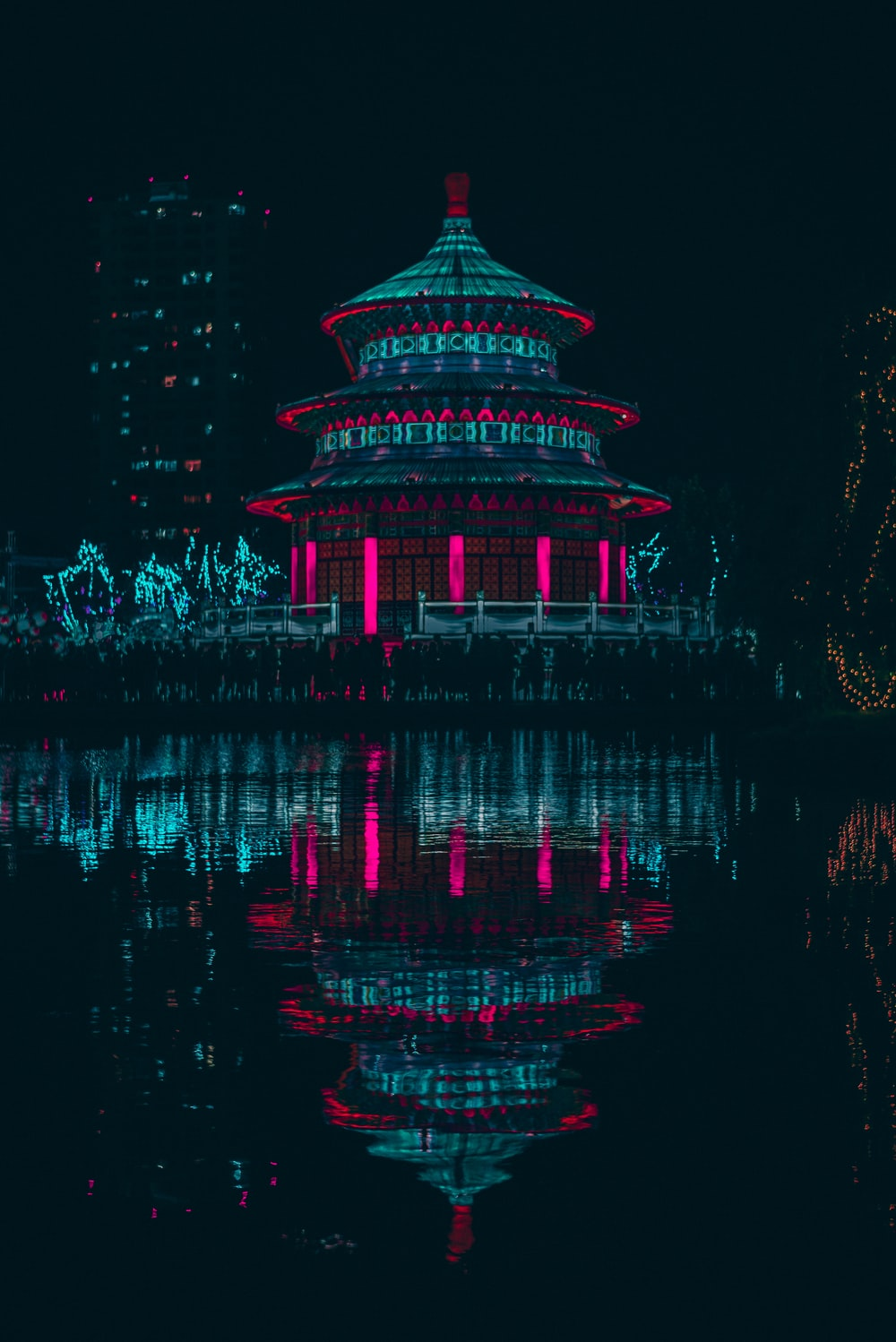 green and red lighted building near body of water during night time