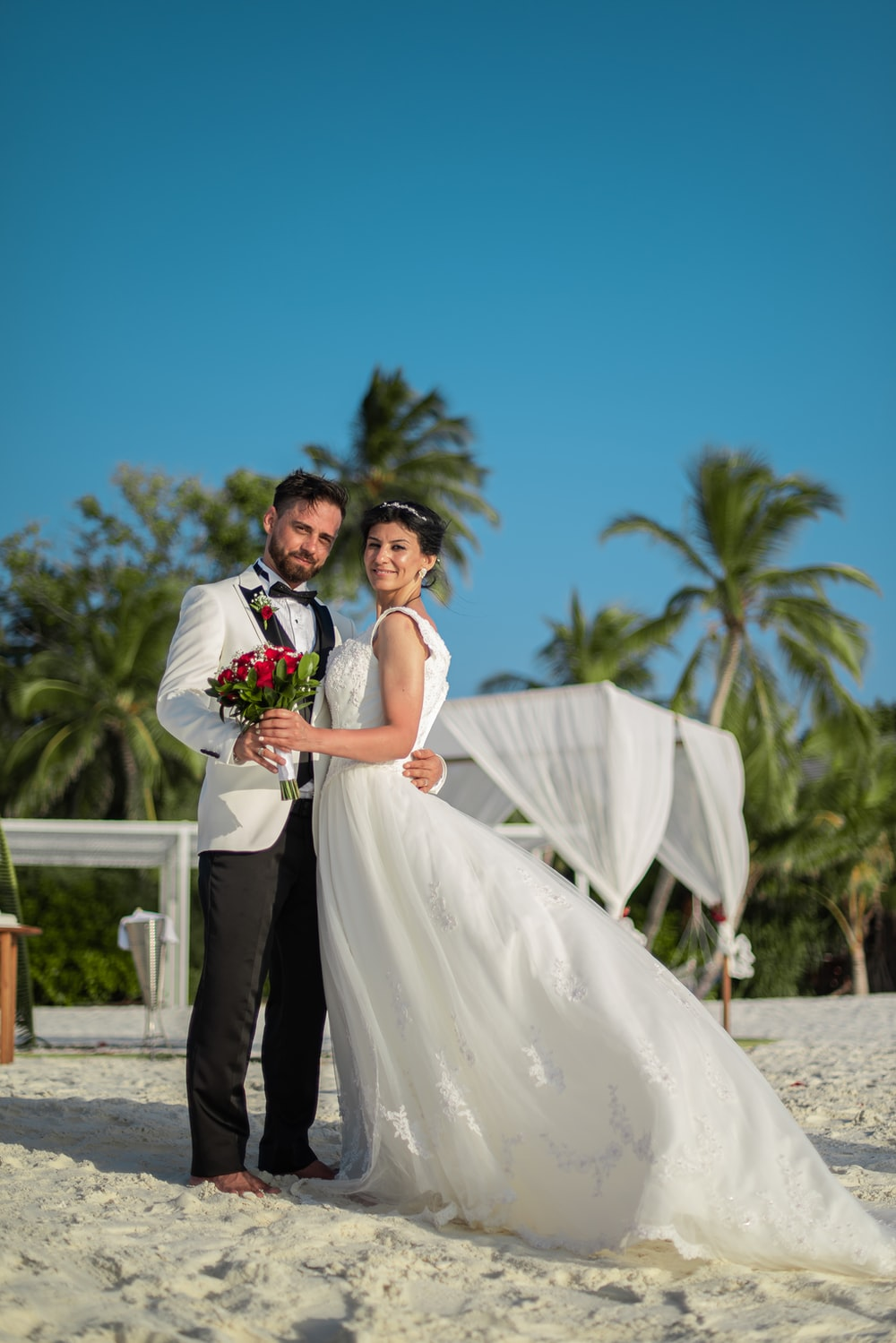 man in black suit and woman in white wedding dress standing on brown sand during daytime