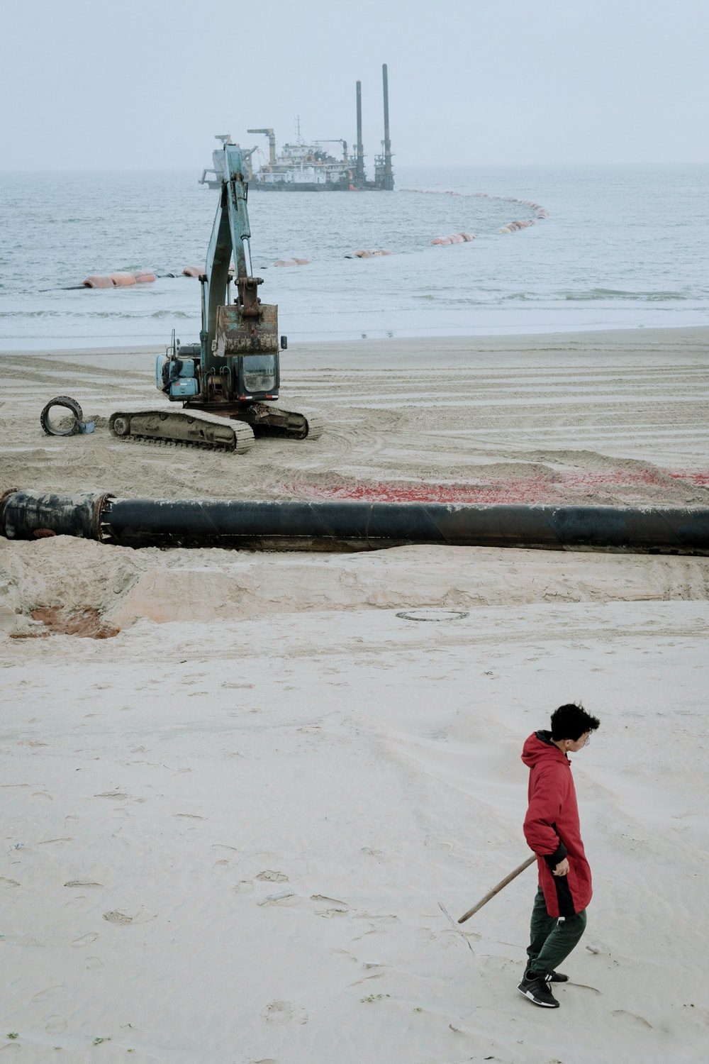 woman in red hoodie standing on beach near black heavy equipment during daytime