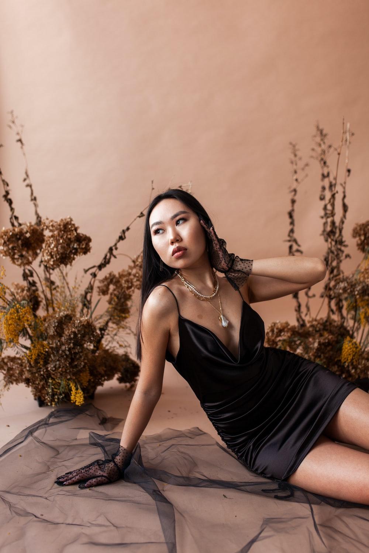 woman in black spaghetti strap dress standing beside brown wall