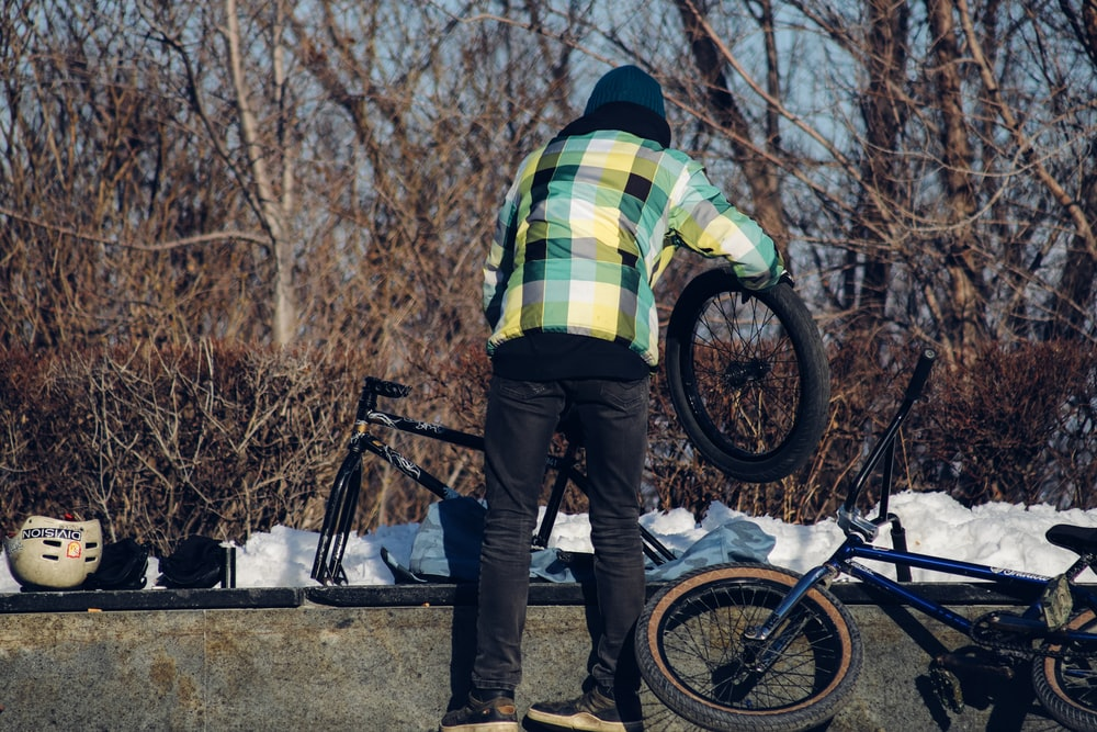 man in blue denim jeans and yellow and blue striped shirt standing beside black mountain bike