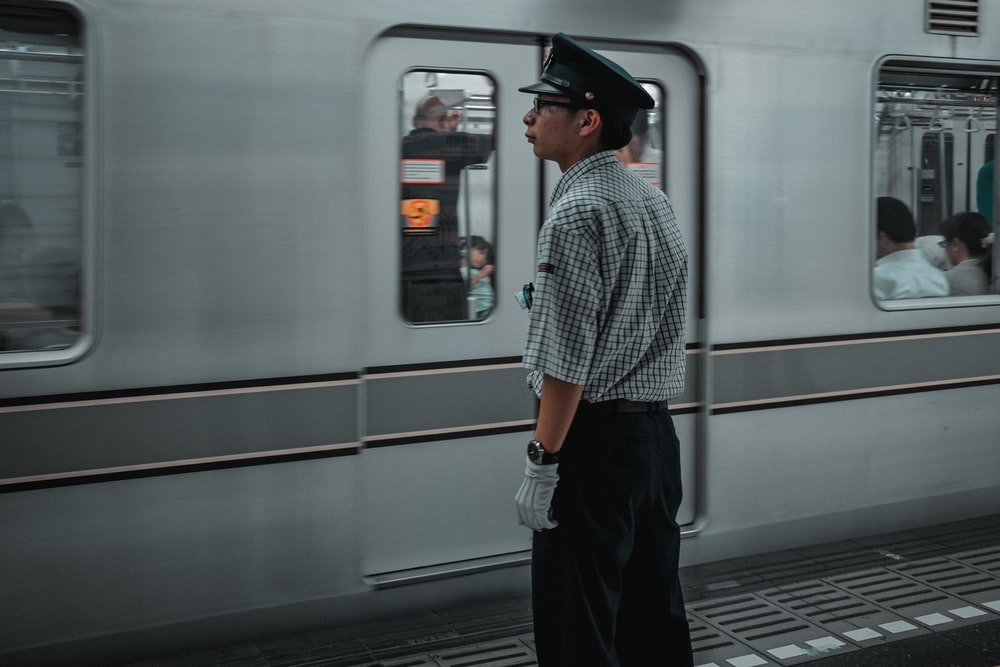 man in black hat standing in front of white train