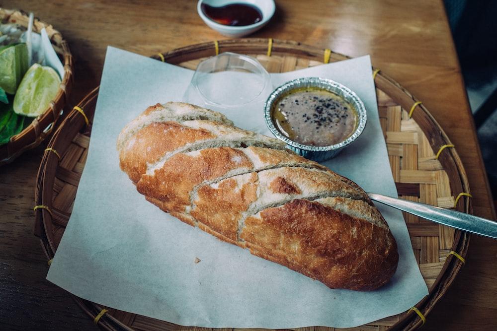 bread on white paper beside white ceramic plate