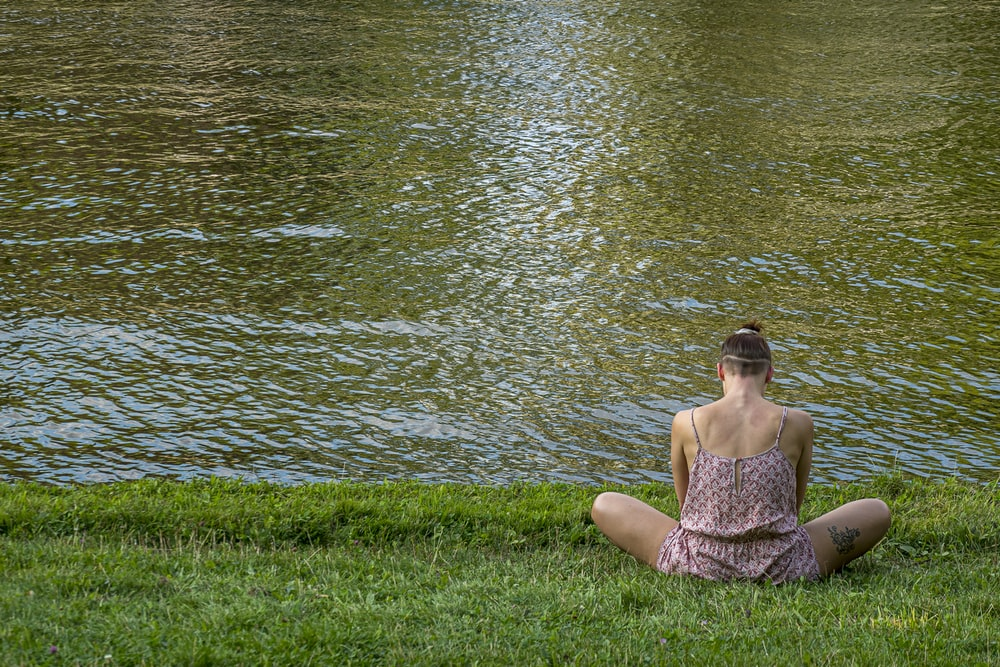 woman in brown tube dress sitting on green grass field near body of water during daytime