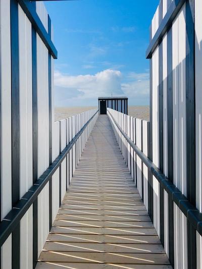 white wooden bridge under white clouds during daytime