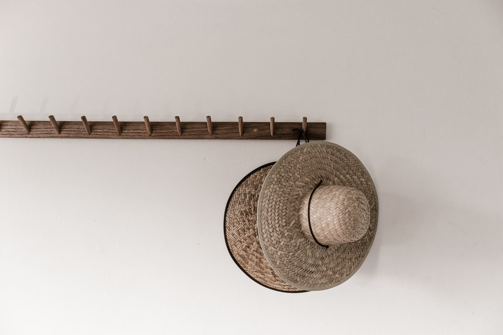 brown straw hat on white wall