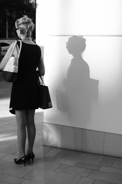 woman in black dress standing beside woman in white coat