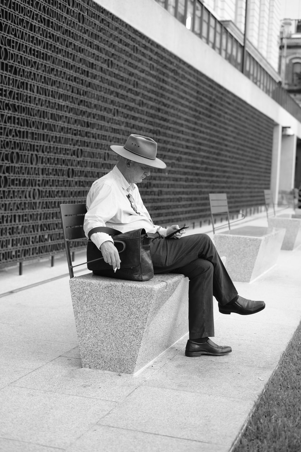 grayscale photo of man in white long sleeve shirt and black pants sitting on concrete bench