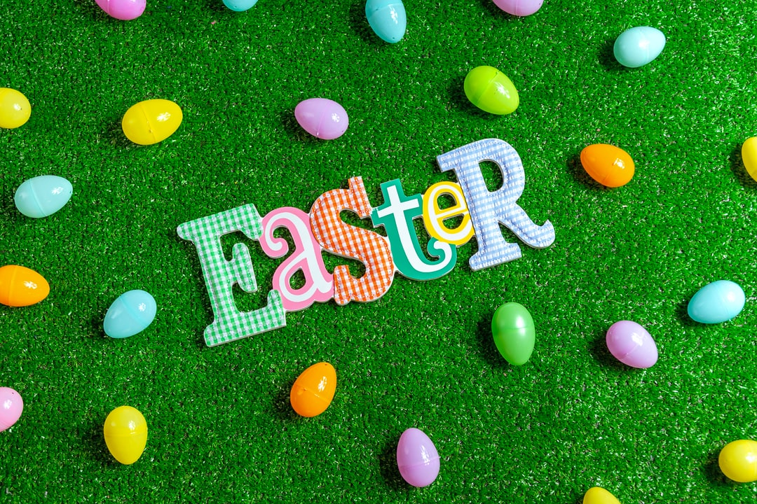 Ester letter text on artificial grass with scattered plastic eggs of pastel colors