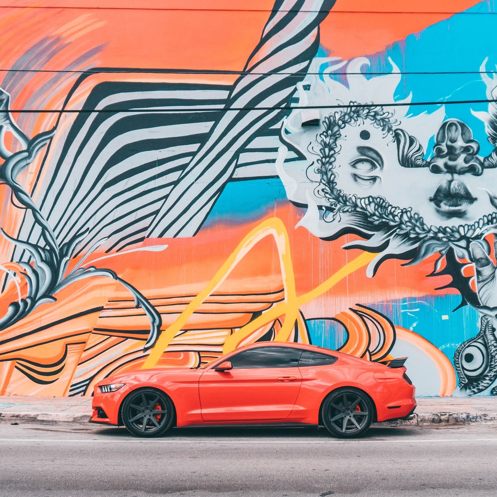 red car parked beside wall with graffiti