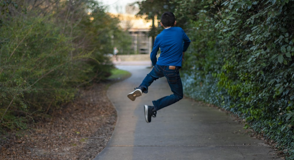 man in blue long sleeve shirt and blue denim jeans walking on gray concrete pathway during