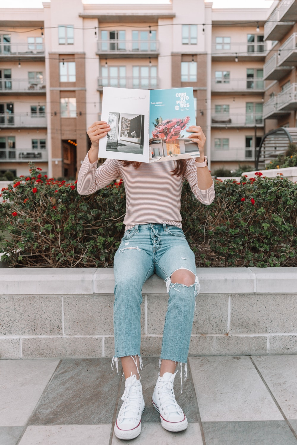 woman in brown long sleeve shirt and blue denim jeans sitting on concrete bench reading book